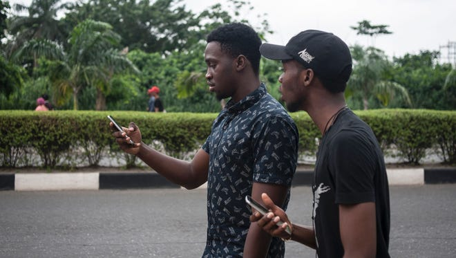 Timi Ajiboye and Tobi Akinnubi use the Pokemon Go application at the University of Lagos.