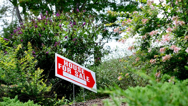 A house for sale sign sits in the landscaping of a house on Gertrude Place in North Asheville on Monday, July 18, 2016.