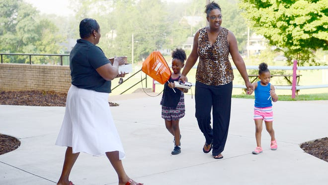 Semaj Winston, 6, left, and Khamryn Lindsey, 4, right, put away their new pencils as their mother Jennifer Linsey, center, walks them into Hall Fletcher Elementary School for the first day on Wednesday, July 20, 2016. Semaj started the first grade and Khamryn will start pre-kindergarten next week.