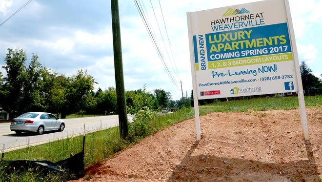 A sign advertises luxury apartments on Monticello Road which are being built in Weaverville near the commercial district which includes a Lowe's and Walmart.