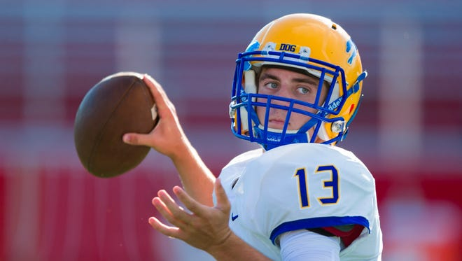Carmel High School junior Jake McDonald (13) warms up his arm during pre-game activities of an IHSAA varsity football game, Friday, Sept. 2, 2016, at Center Grove High School.