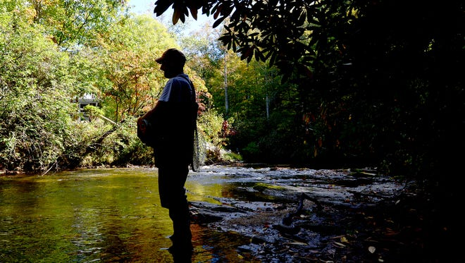 Matt Christian, an education specialist with the North Carolina Wildlife Resources Commission, watches his student, Giles Simpson (not pictured), fish during an introduction to fly fishing class on the East Fork of the French Broad River near Rosman.