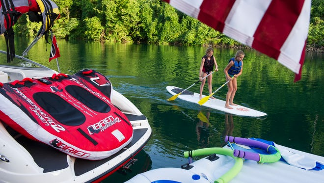 Katie Tuten, left, and Sarah Pridham, both of Atlanta, Ga., propel a paddle board on Norris Lake Wednesday, July 8, 2015, at Norris Dam Marina. From the first dam project to construct Norris Lake in 1933,  the Tennessee Valley Authority has created reservoirs that encompass 650,000 surface acres of water, producing 11,000 miles of shoreline.