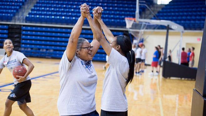 UNCA point guard Ja'Da Brayboy high fives participant Venita Brown Monday at the basketball fantasy camp held by the women's basketball team.