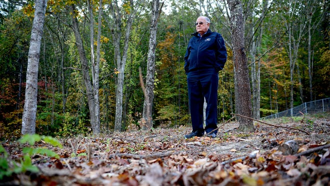 Jerry VeHaun, emergency services director, stands in the County Home Cemetery, a potter's field, where the bodies of those buried in the original pauper's cemetery, where Erwin High School now stands, were moved.
