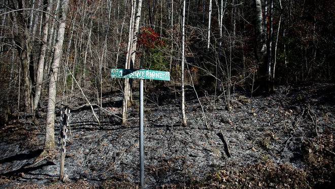 A street sign and vegetation show the marks of the fire that was burning there only couple days ago.