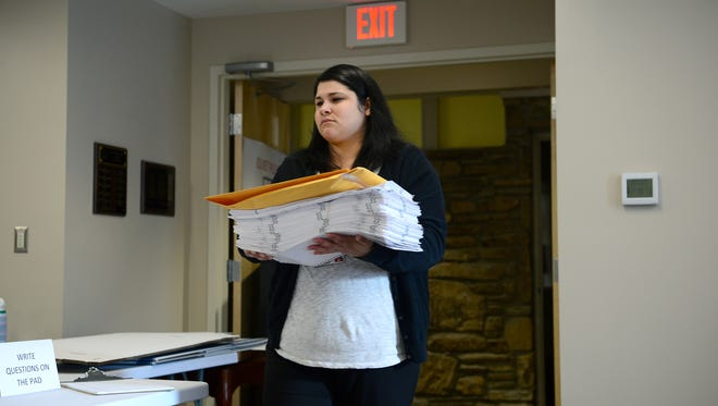 Victoria Leyva carries in a stack of ballots so a recount can begin at the Buncombe County Elections building on Wednesday, Dec. 7, 2016.