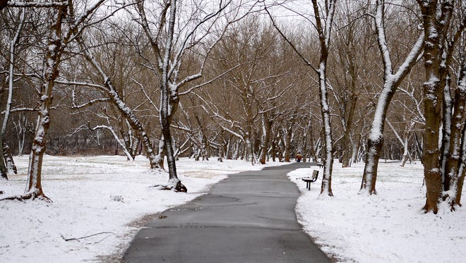 Snow lightly blankets either side of the path at the French Broad River Park on Friday, Jan. 6, 2017.