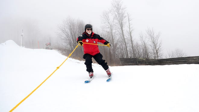 Chuck Quillen holds on to the line attached to a sled as he demonstrates how hurt skiers are transported down the mountain by the ski patrol at Wolf Ridge Ski Resort on Wednesday, Jan. 11, 2017. Quillen has been on the ski patrol for 15 years.