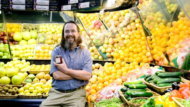 Walter Harrill, of Imladris Farms, holds a jar of his locally-made jam in the produce section of the French Broad Food Co-op where it is sold in downtown Asheville. The co-op is one store that has been successful in getting truly local products to market.