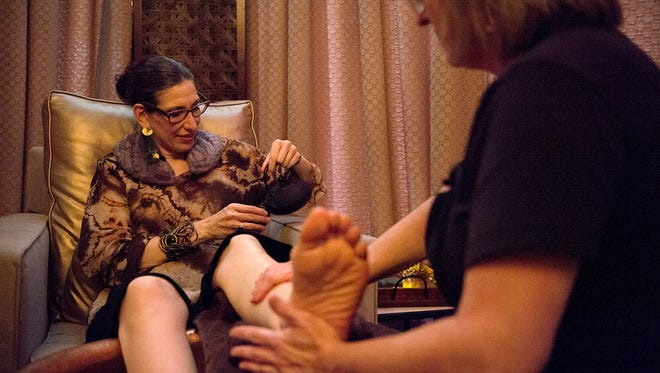Regular customer Lisa Stendig, owner of The Goddess Shop in the Grove Arcade, pours herself some tea while receiving a foot massage from massage therapist Genny Gray Tuesday evening April 18, 2017 at the Wake Foot Sanctuary.