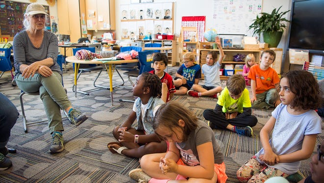 First grade teacher Patti Evans sits with her class as they talk about the golden silk spider at Isaac Dickson Elementary. The students researched the spider for a bill to make it the North Carolina state spider, an opportunity to learn about nature and also the legislative process. The bill was passed in the House and moves onto the Senate.
