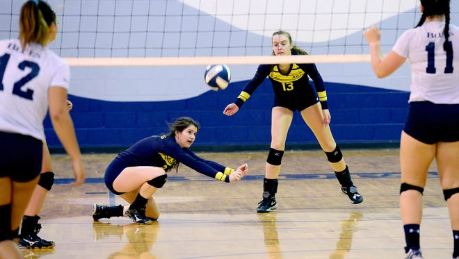 Asheville Christian Academy's Sarah Buchanan, left, goes low for a pass in front of Kate Condra, right, during their match at Asheville School on Tuesday, Sept. 6, 2016. The Lions defeated the Blues in three sets, 25-15, 25-17, 25-14.