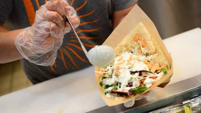 A Doner kebab of beef and lamb on bread is assembled at The Doner Kebabs & Falafels inside the food court of the Asheville Mall on Friday, Sept. 15, 2017.
