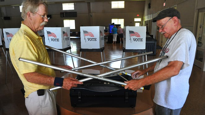 Poll worker Chip Whitney (left) and Precinct Clerk George Blessington assemble a touch screen electronic voting machine alongside the 11 paper ballot voting booths for Precinct 34 at the John A. Crowley Center, 2355 82nd Ave. in Vero Beach, in 2014.