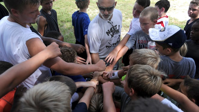 """Bill Motta (center), St. Edward's School football coach, rallies players in the Victory Kids Football Camp after a motivational talk before heading back to the football field for more drills at the Gifford Youth Activities Center in this 2013 file photo. """"It's great, anytime we have an opportunity to influence some young people for God,"""" Motta said. """"The athletic performance in football provides a platform for us to get these guys foundationally sound athletically and give them a taste of what's the right thing to do spiritually and academically as well."""""""
