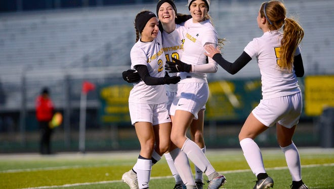 Reynolds players (from left): Pali Smith, Clara Kintner, Annabelle Sparks, and Sarah Groce celebrate a goal on North Henderson during the first half of their game at Reynolds High School on Wednesday, March 7, 2018. The Rockets defeated the Knights 9-0 in almost 45 minutes of play.