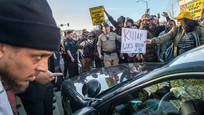 """Protesters surround a police car as they shut down Interstate 5 in both directions in downtown Sacramento, Calif., Thursday, March 22, 2018. Protesters decrying this week's fatal shooting of an unarmed black man marched from Sacramento City Hall and onto the nearby freeway Thursday, disrupting rush hour traffic and holding signs with messages like """"Sac PD: Stop killing us!"""" (Renee C. Byer/The Sacramento Bee via AP)"""
