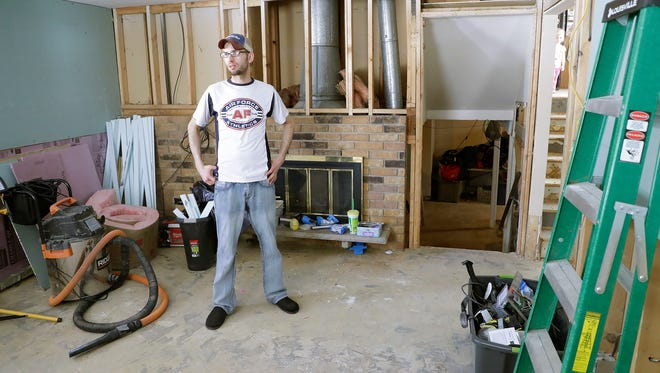 Matt Sorenson stands amid the debris in the heavily damaged family room of his tri-level house at 3152 St. Gregory Drive Friday, April 20, 2018 in Green Bay, Wis. The home was flooded with approximately 55 inches of water in February.