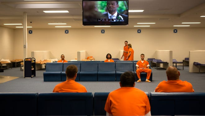 Inmates watch television in one of the newer intake areas at the Larimer County Jail Thursday, Oct. 9, 2014.