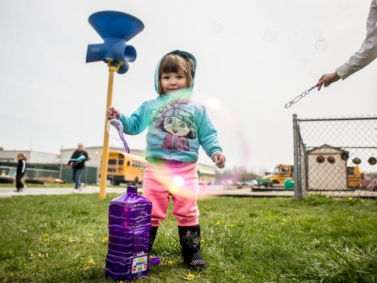 Brooke Medlin, 2, blows bubbles along with her mother, Julie Medlin, of Fair Haven, during the Community Kite Day Saturday, April 30, 2016, at Pointe Tremble Early Childhood Center in Algonac.
