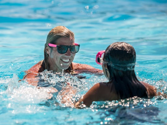 Tracy Lazzara, of Algonac, swims with her daughter,