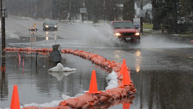 Traffic negotiates the high water across Route 47 at County Road VV in Keshena December 16, 2014.  As of noon, road closed signs were erected on Route 47.