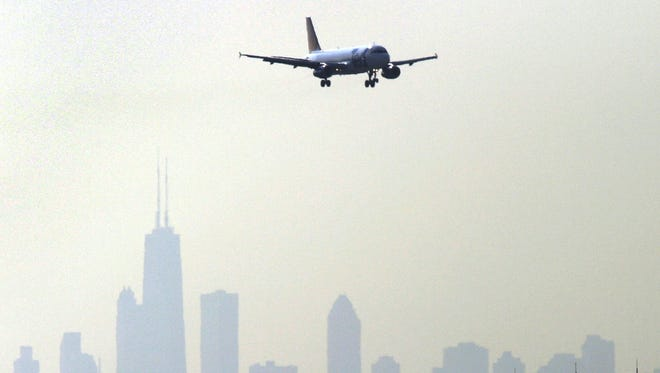 The Chicago skyline is silhouetted in the background as a plane descends comes in to land at O'Hare International Airport on July 15, 2004.