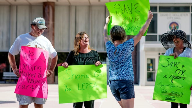 Patrice Drainville, second from left, smiles as Kristi Doe, center, parades around with a sign while protesting the possible closure of the Lansing City Market on Monday, July 9, 2018, outside Lansing City Hall. Looking on at left is Vic Doe and Joni Holmgren, at right. The rally was organized by Drainville, vice president of operations for the Waterfront Bar and Grill, a City Market tenant that is concerned about the end of its lease.