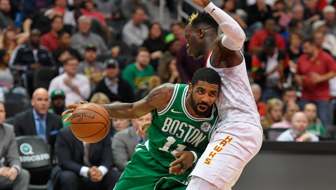 Boston Celtics guard Kyrie Irving (11) runs into Atlanta Hawks guard Dennis Schroder (17) during the second half at Philips Arena. Mandatory Credit: