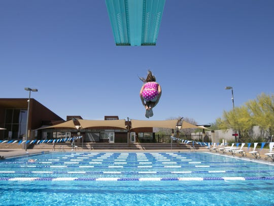 A girl jumps off a high diving board at the McDowell