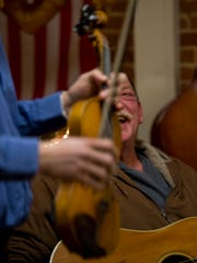 Mike Krantz, co-host of the monthly 3rd Thursday Bluegrass Jam at The Gathering Place in Boonville, Ind., congratulates fiddle player Kevin Bowlds of Knottsville, Ky., after a particularly good jam Thursday night.