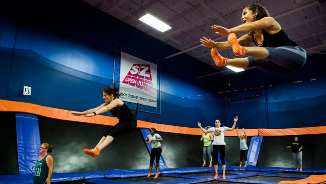 Devon White (right) touches her toes in the air as she leads a trampoline aerobics class at Skyzone in Newark on Wednesday evening.