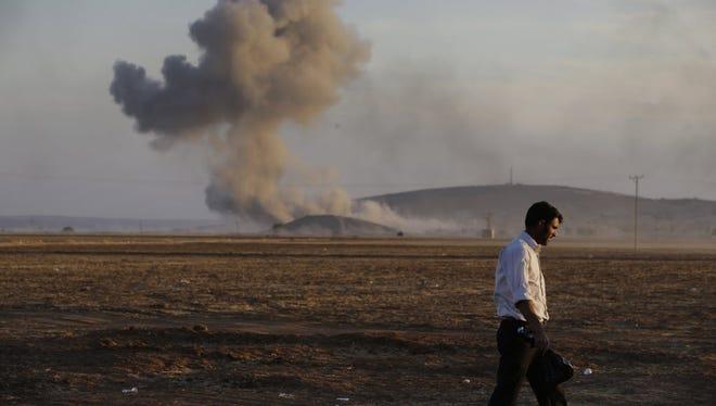 A Turkish Kurd walks away as airstrikes hit Kobani, inside Syria, as fighting intensifies between Syrian Kurds and the Islamic State militants.