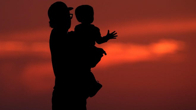 A man and his son are silhouetted against the sky Friday as they watch the sunset from a park in Kansas City.