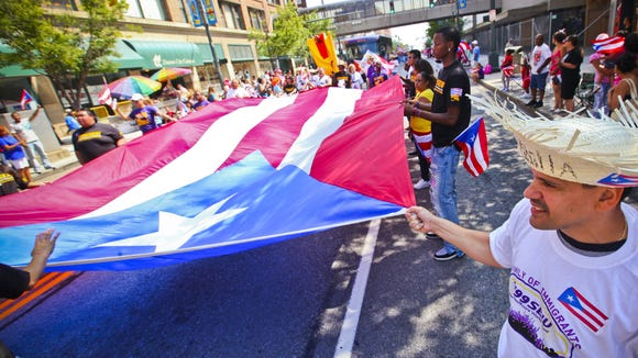 Participants hold the Puerto Rican flag during the 41st Puerto Rican Parade in Rochester in 2010.