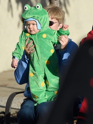 Theresa Garlet of Evansville helps her 10 month-old grandson Conner Duff wave to parade participants as they pass during the 2016 Evansville Christmas on North Main Parade in Evansville Sunday.  An estimated 10,000 people lined the streets to watch the event this year, according to organizers.
