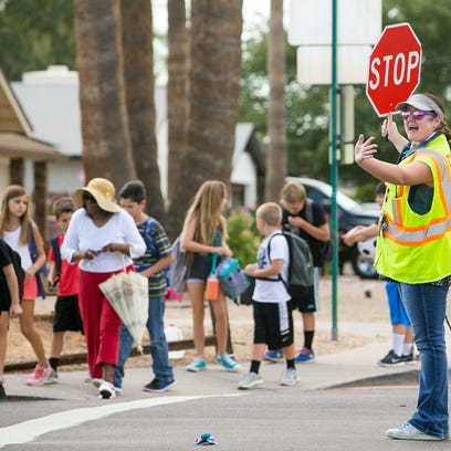 Crossing guard Samantha Maskey helps parents and students