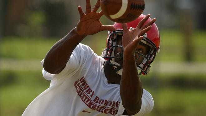 Vero Beach High School's A.J. Ausby, 17, catches a pass during a Sept. 29, 2004 practice, the first workout since school was canceled for Hurricane Jeanne. With Hurricane Irma threatening Florida, all nine area games have been postponed or canceled this week.