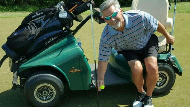 Jim Bubb, who is paralyzed from the waist down, removes the ball from the cup after his hole-in-one at Forrest Crossing Golf Course this past week.