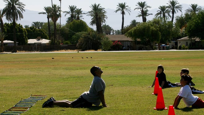 Football coach Brian Dominguez (left), from the Desert Recreation District, leads players in a stretch during the football skills camp at Miles Avenue Park on Monday, June 28, 2010 in Indio, Calif.