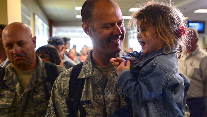 Vermont Air National Guard Staff Sgt. Shawn Robbins of Swanton holds his 2-year-old daughter Eliza at Burlington International Airport on Monday, April 17, 2017, after returning from a six-month deployment.