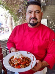 Chef Jorge Gonzalez of The Village Pub with an orange chicken dish.