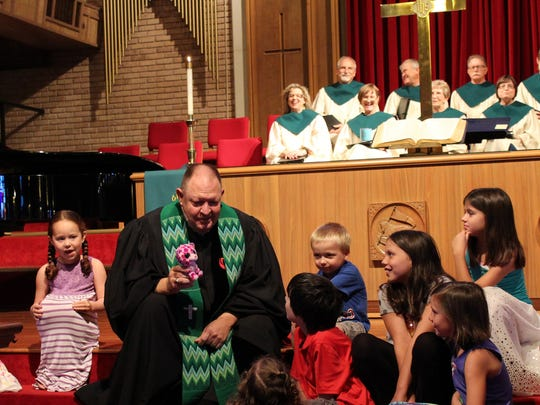"""The Rev. Gary Boles gives a lesson to youngsters based on an item he found in the """"Stump the Pastor"""" bag at his first service at Aldersgate UMC."""
