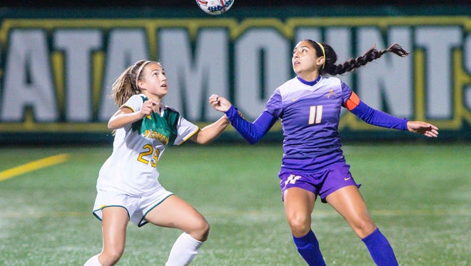 The University of Vermont's Maddie Masengarb, left, and the University of Albany's Vivian Vega follow the ball in Burlington on Thursday, October 12, 2017.