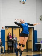 Harper Creek's Olivia Leson serves the ball during
