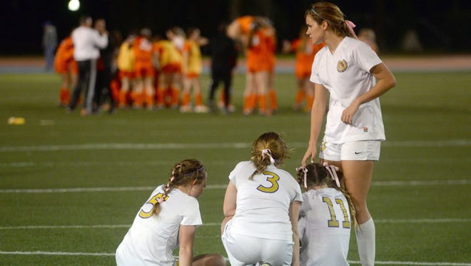 Taylor Arnold, Allison Cannon, Maggie Weldon and Kyra Montes huddle together as Mt. Carmel celebrate their 2-1 win for the LHSAA Division 1 championship.