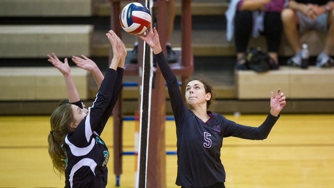 Henderson County's Morgan Farris (5) hits the ball past Owensboro Catholic's Alli Thompson (38) during the Jerry Mezur Spikefest at Henderson County High School in Henderson, Saturday, Oct. 8, 2016. Henderson County beat Owensboro Catholic 2-0.