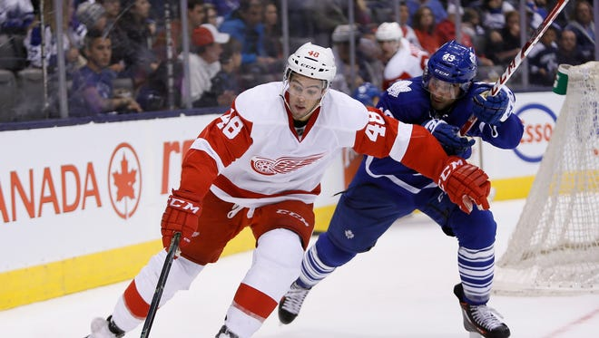 Oct 3, 2015; Toronto, Ontario, CAN; Detroit Red Wings defenseman Ryan Sproul (48) carries the puck past Toronto Maple Leafs forward Nazem Kadri (43) at the Air Canada Centre. Detroit defeated Toronto 2-1.