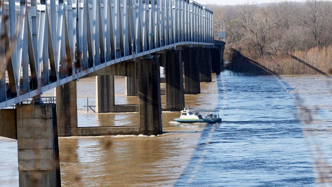 A small boat maneuvers along the Mississippi River, below the newer bridge in Vicksburg, Miss., Wednesday, Jan. 13, 2016. Two more barges hit a railroad bridge nearby just after noon as the Mississippi River's high water continues to play havoc with shipping.